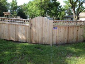 Custom wood fence with cube lattice and arched gate in Sioux City, IA