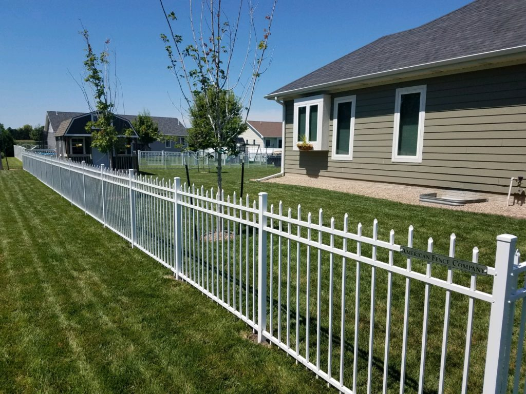 American Fence Company nameplate mounted on a white ornamental iron fence