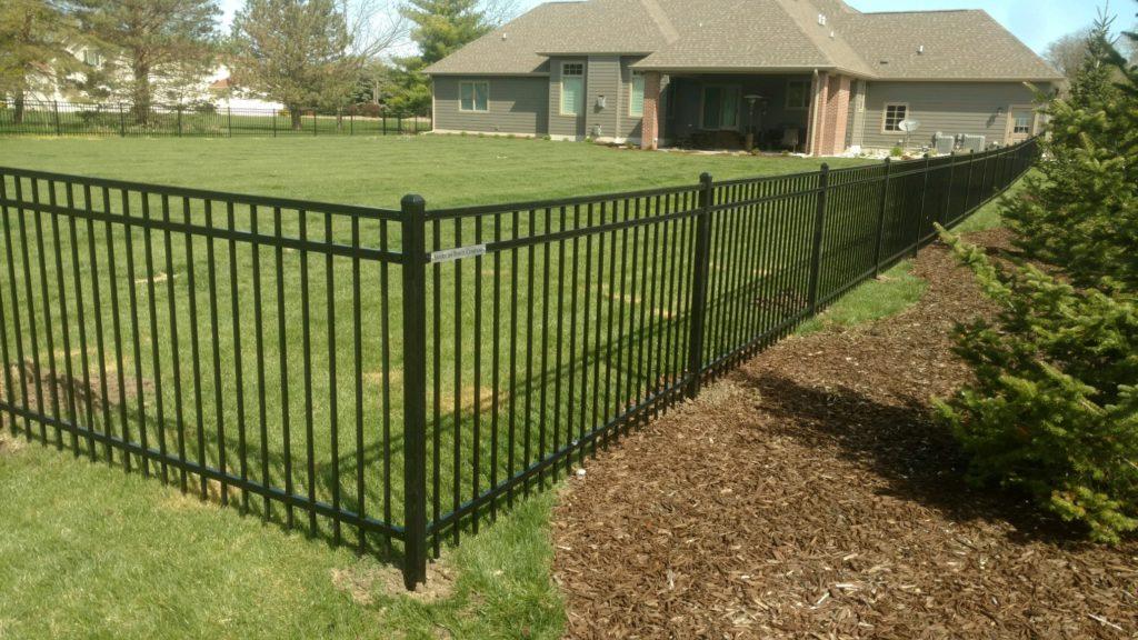 Black flat top ornamental fence around a residential back yard